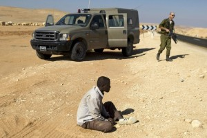 An African man is detained by Israel's military after crossing illegally into Israel from Egypt, north of Eilat